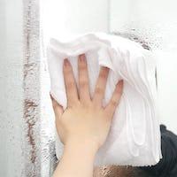 布で鏡の表面をふき取る